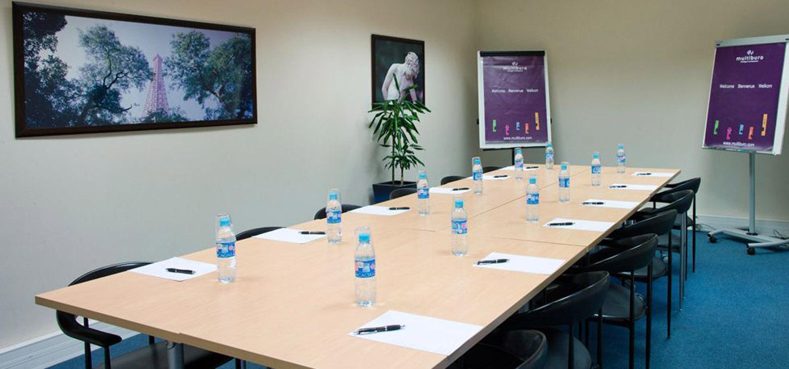 salle de réunion pour douze personnes avec bouteilles d'eau et tableau blanc à louer dans Paris