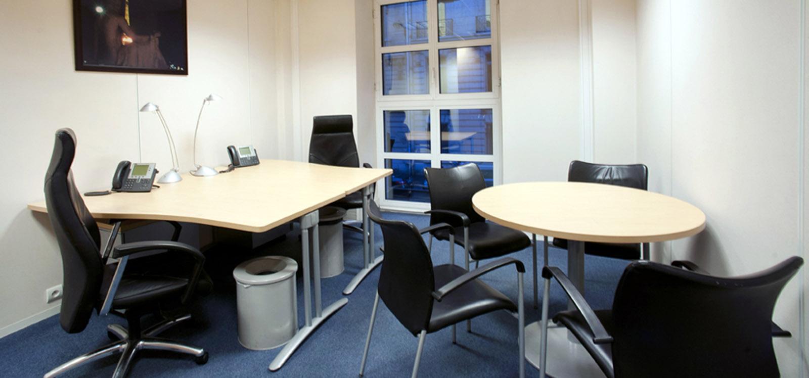 bureau à louer à Paris avec deux postes de travail et une petite table de meeting  dans un espace au mobilier de bureau minimaliste équipé d'une large fenêtre