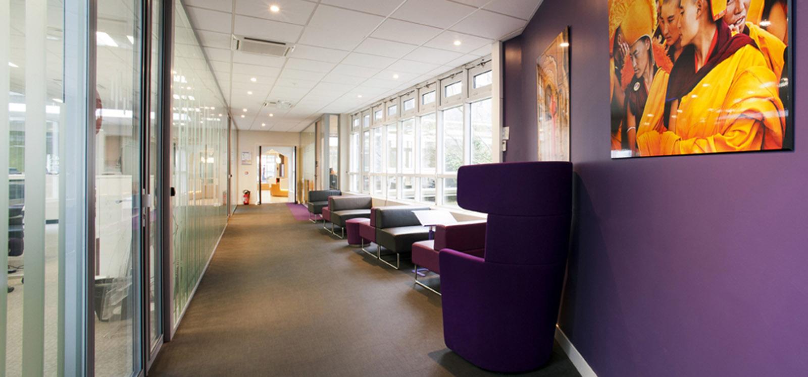 espace de détente avec de multiples fauteuils coloré et confortable dans un cadre moderne en face de larges fenêtre offrant une belle lumière