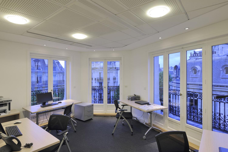 trois postes de travail dans un bureau lumineux en open space avec de larges fenêtres à Paris