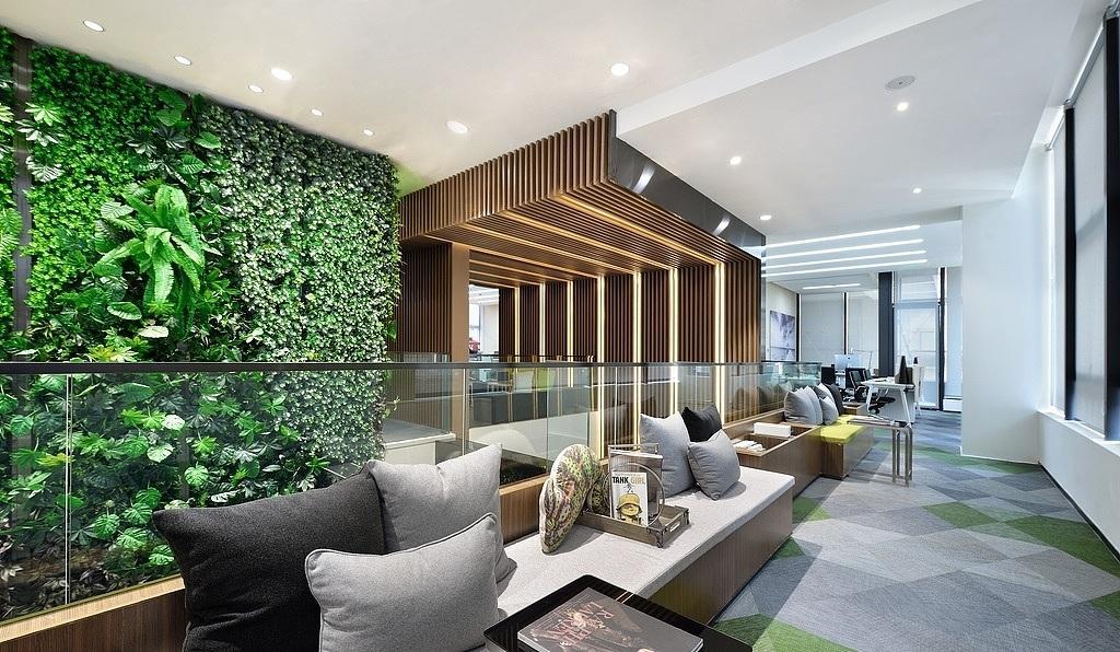 Espace de détente en commun avec fauteuils confortable et plusieurs coussins et un espace verts dans une ambiance chaleureuse et une décoration moderne et chaleureuse dans un business center à Suresnes