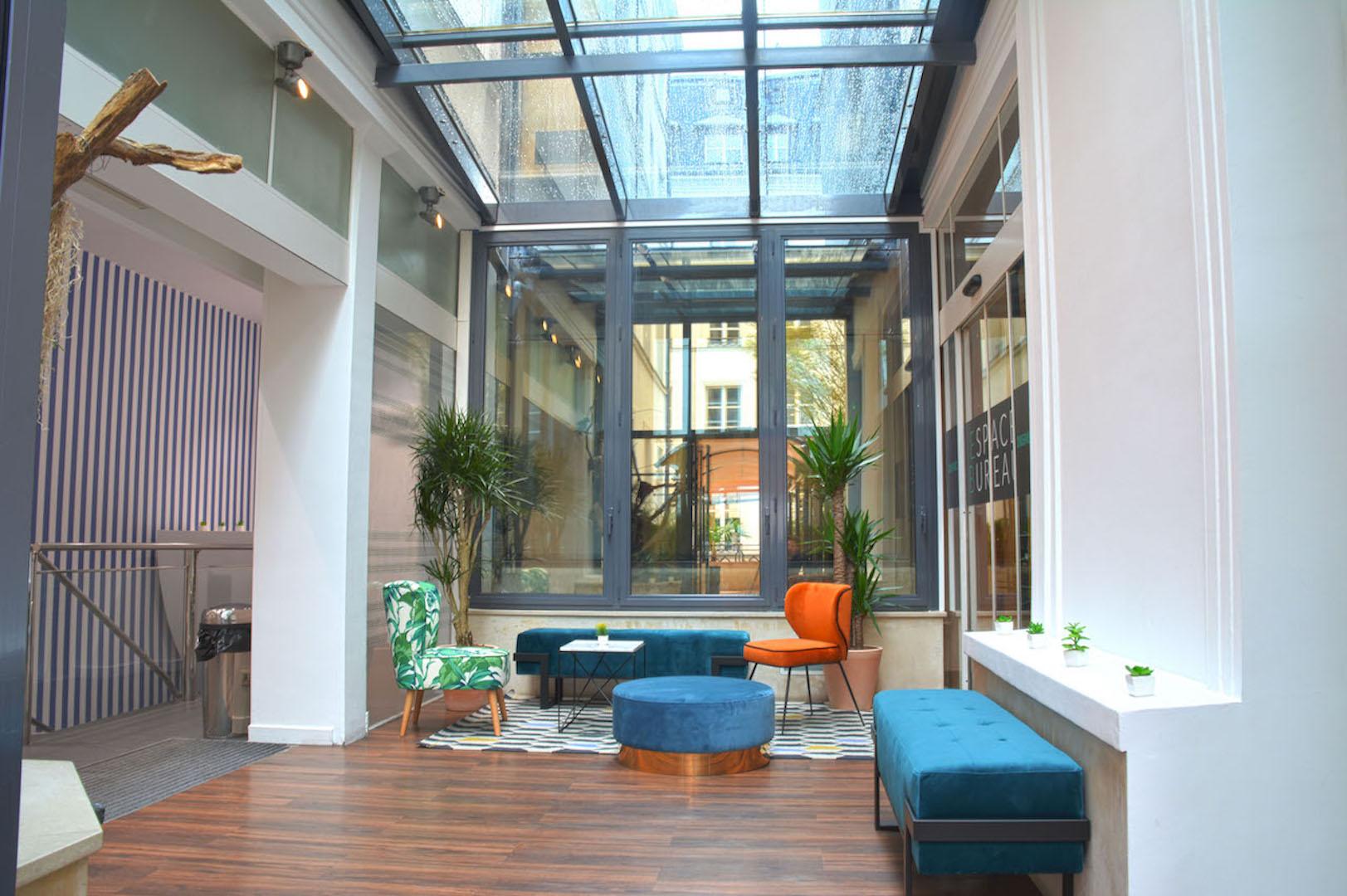 espace de détente avec fauteuil confortable et coloré et une ambiance chaleureuse avec fenêtre au plafond donnant vue sur le ciel et plantes vertes à Paris