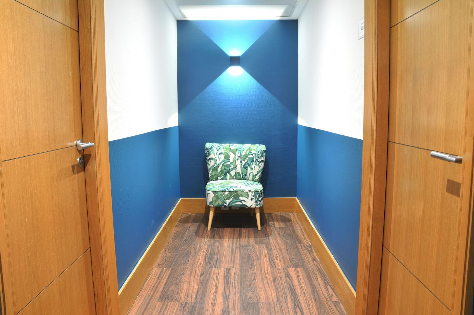 couloir avec fauteuil confortable et mur coloré en bleu et blanc dans un business center proposant des bureaux à louer dans Paris