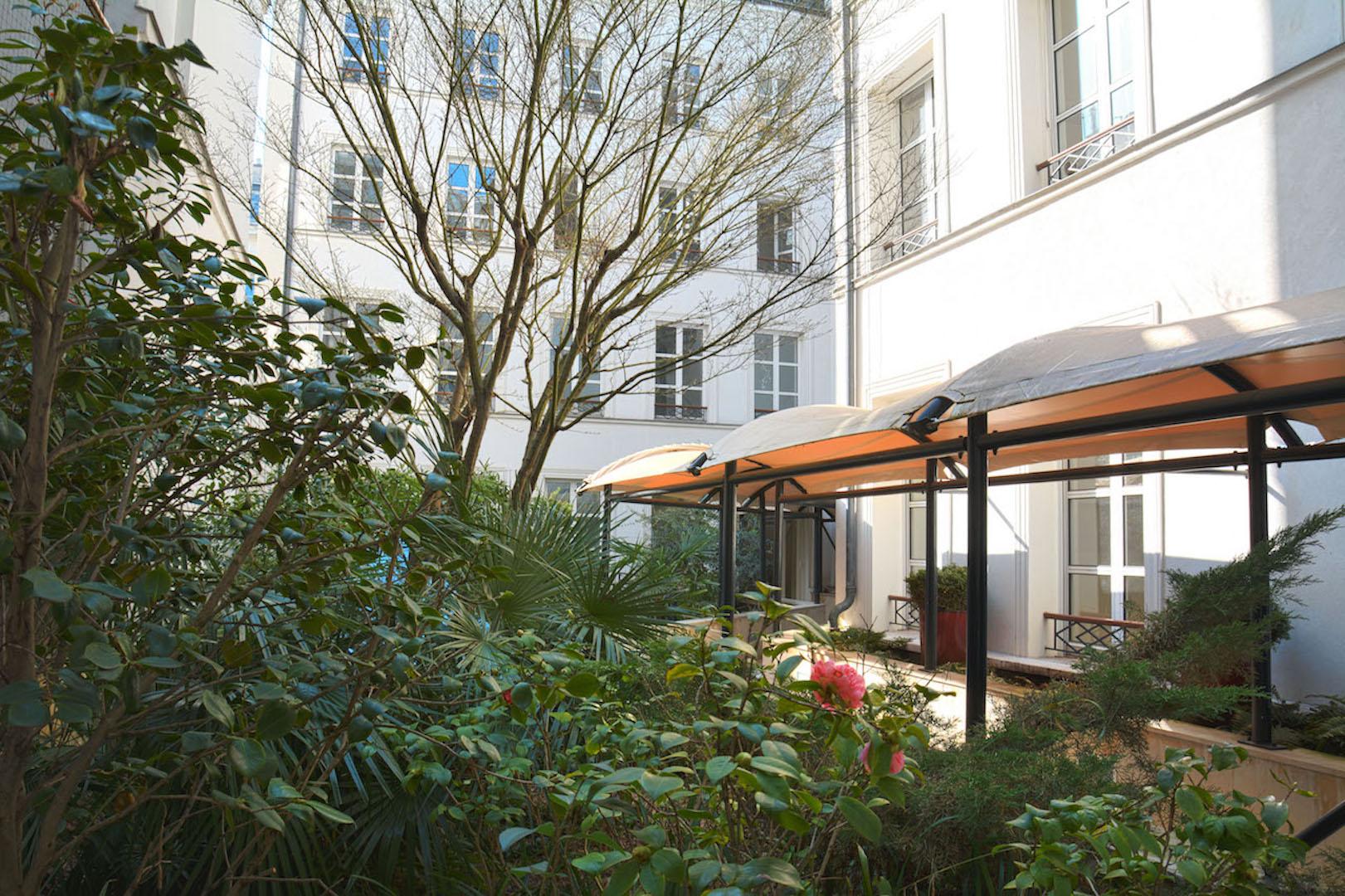 extérieur du business center avec espaces verts donnant sur des batiments traditionnelles de Paris