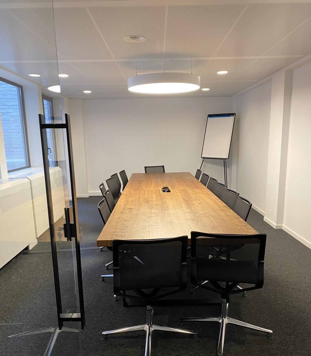 Vergaderzaal met lange vergadertafel en stoelen