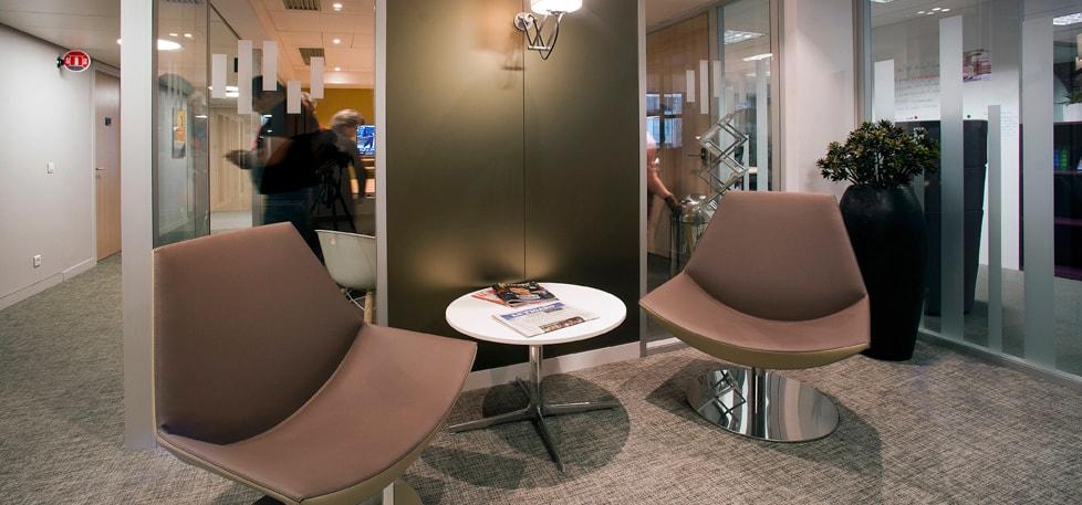espace d'attente à l'accueil avec deux sièges confortables ainsi que des magazines